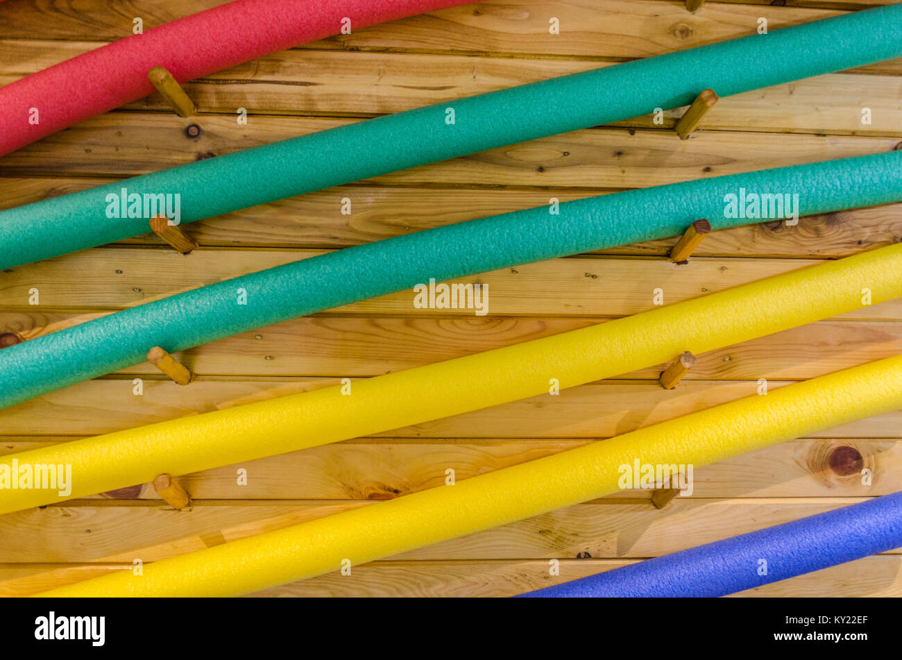 Colorful hydrotherapy pool foam noodles kept over wooden background. - Stock Image