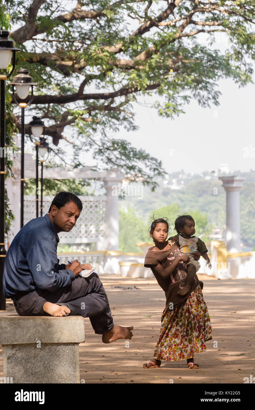 Indifference the root of Inequality: Gentleman sitting on bench looks away from a poor, shabbily dressed young girl - Stock Image