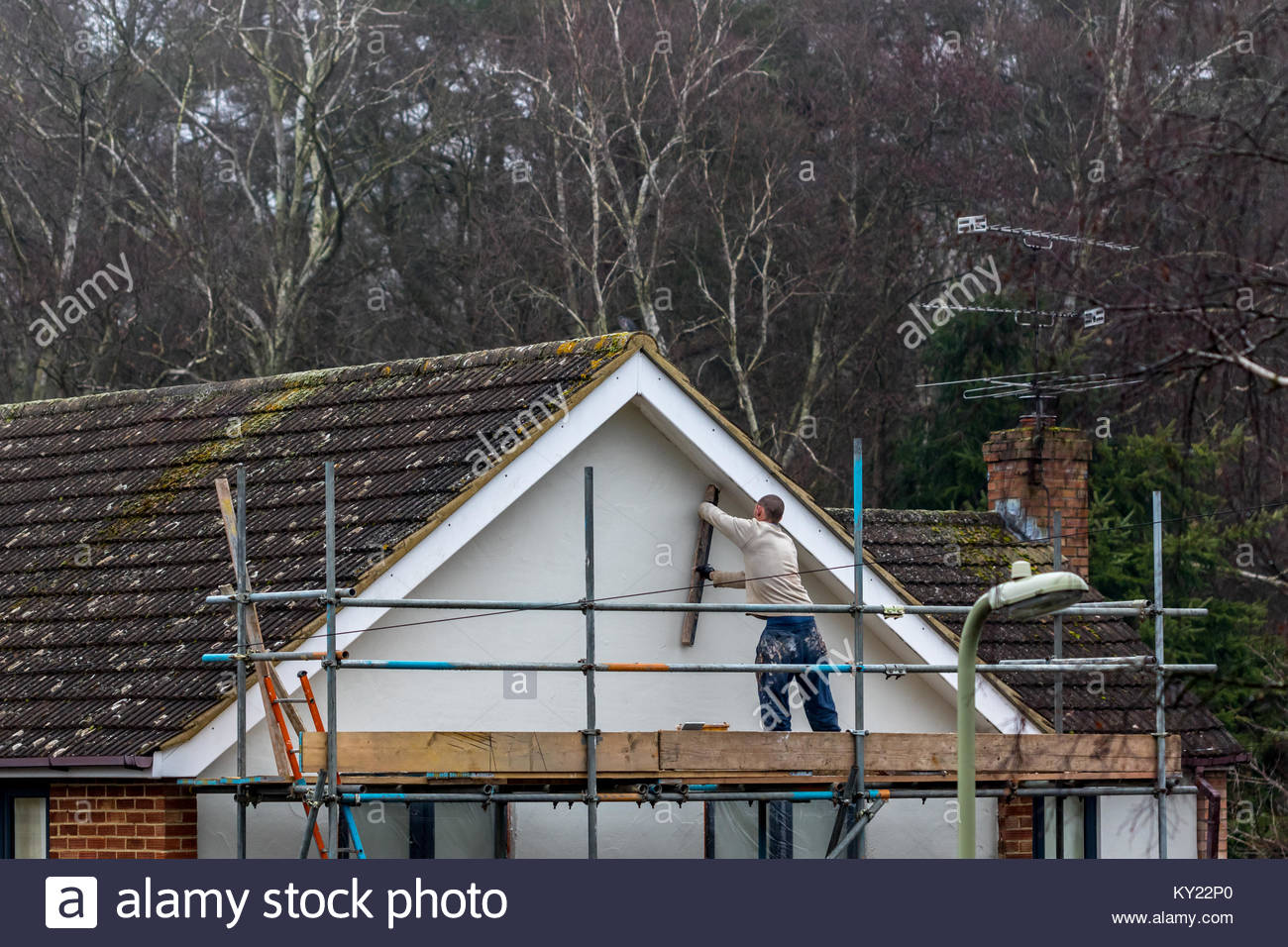 A workman using a long wooden spatula to apply the finishing touches to the white rendering on the gable end of - Stock Image