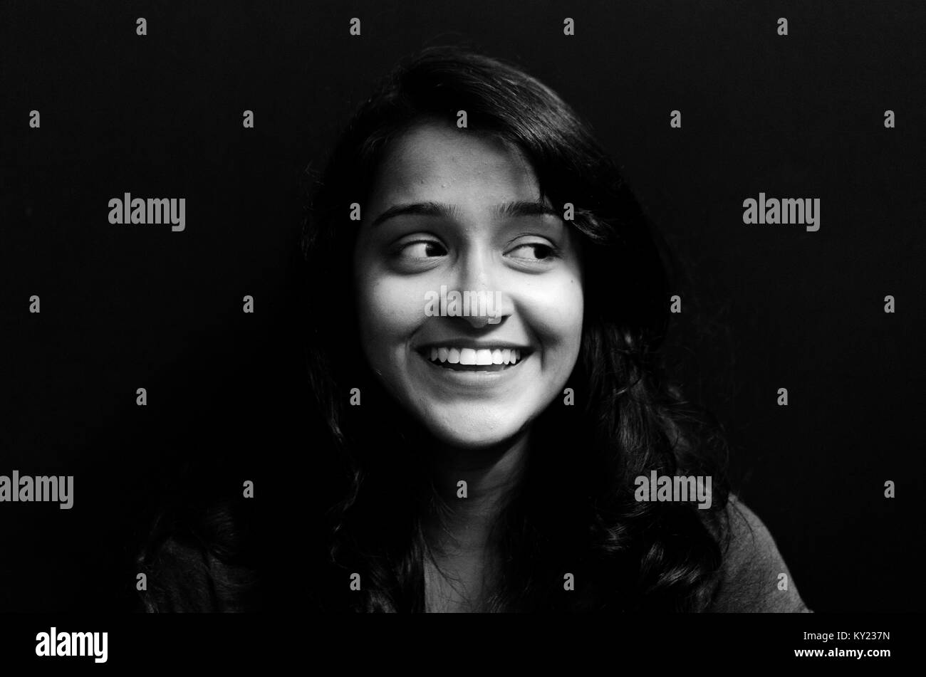 Black and white portrait of a cute, chubby girl looking away, smiling, over black background. - Stock Image