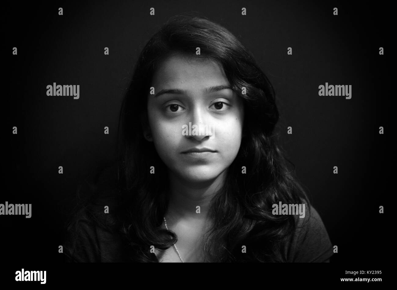 Black and white portrait of a cute chubby indian girl giving a blank stare over