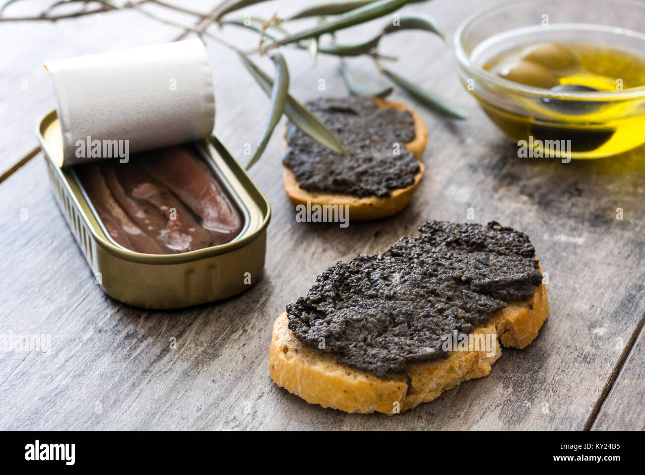 Black olive tapenade with anchovies, garlic and olive oil on wooden table - Stock Image