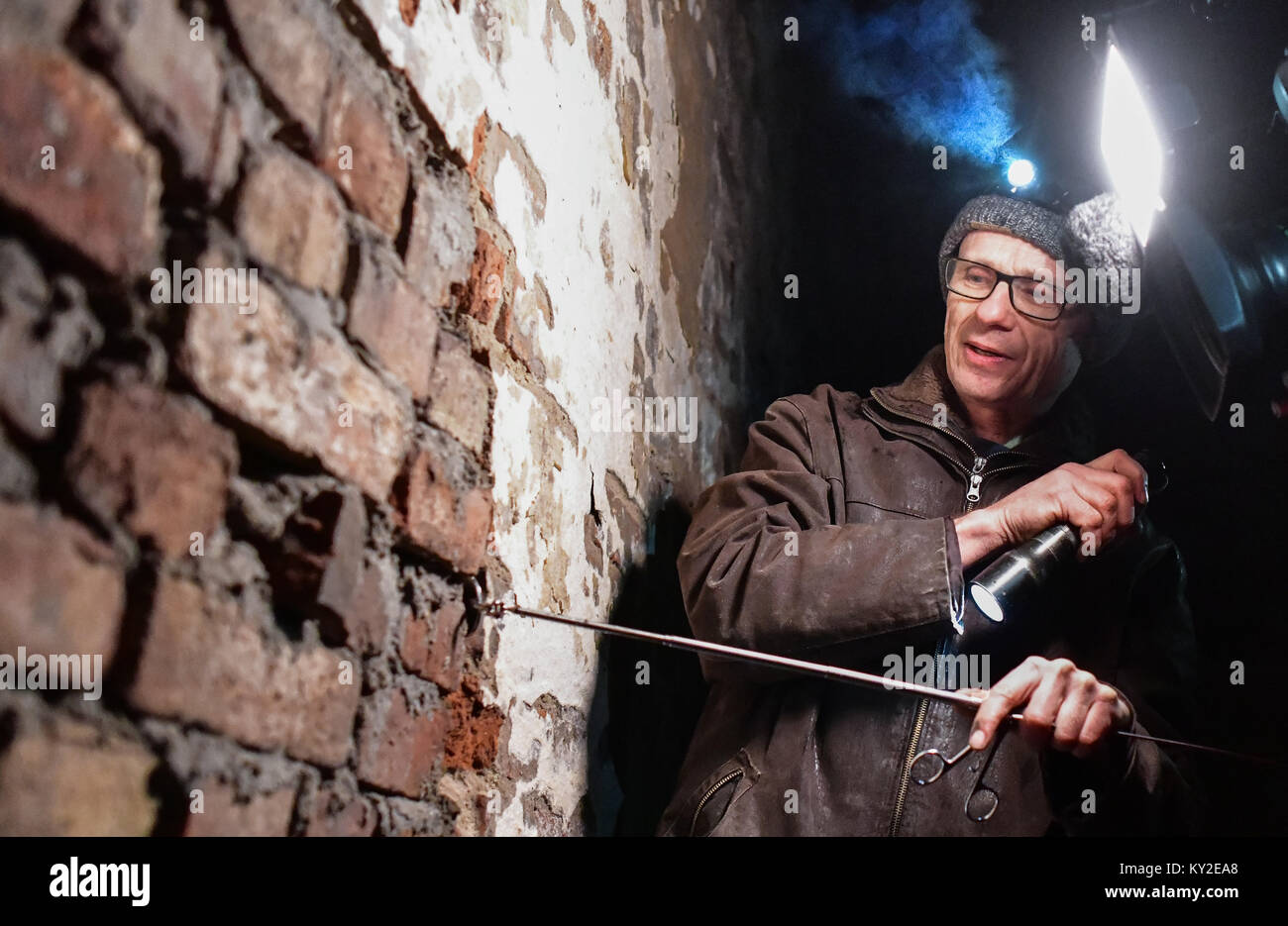 Oder, Germany. 12th Jan, 2018. NABU-conservationist Lutz Ittermann uses a torch to search for bats in an old brewery - Stock Image