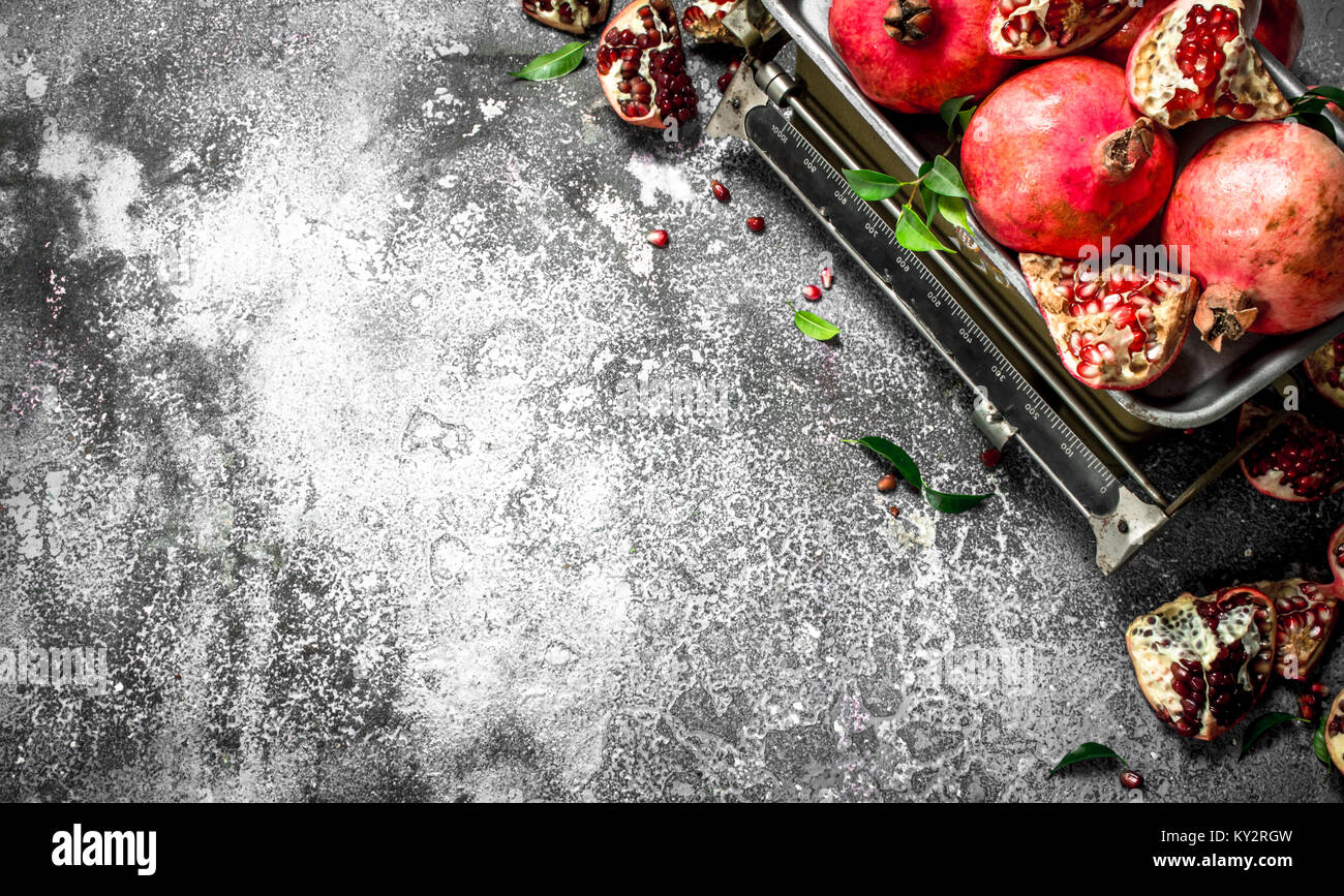 Ripe pomegranates on the scales. On a rustic background. Stock Photo