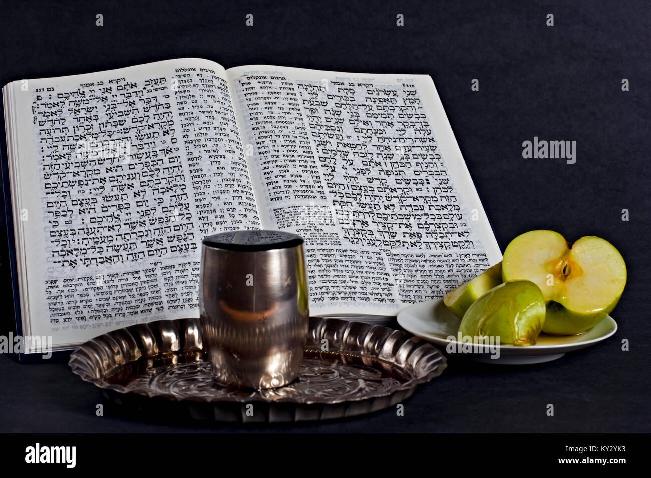 Jewish concept. A still life of a Prayer book, Apple, Honey and a wine goblet - Stock Image