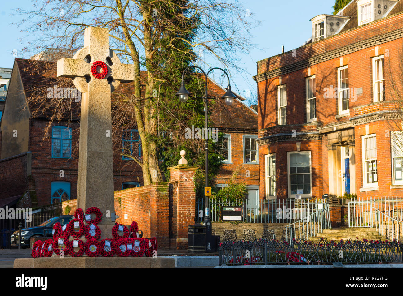 Bury St Edmunds War Memorial at Angel Hill - WW1 And WW2 Cross - with wreaths of poppies. Suffolk, England, UK - Stock Image