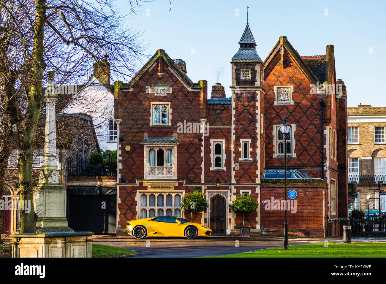 Yellow Lamborghini parked outside grand old house on Chequer Square next to the Norman tower & facing the Great - Stock Image