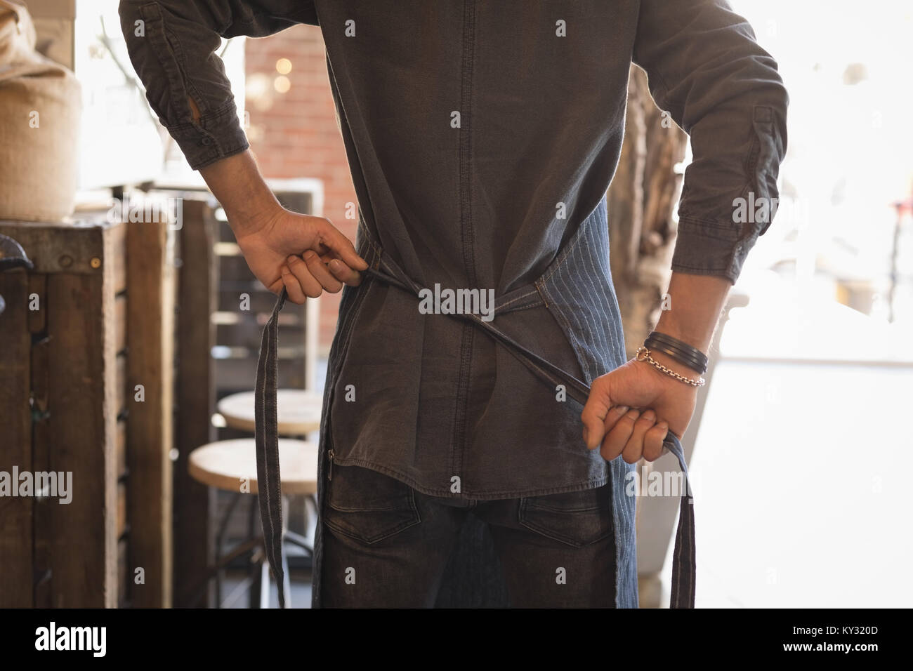 Waiter tying apron in coffee shop - Stock Image