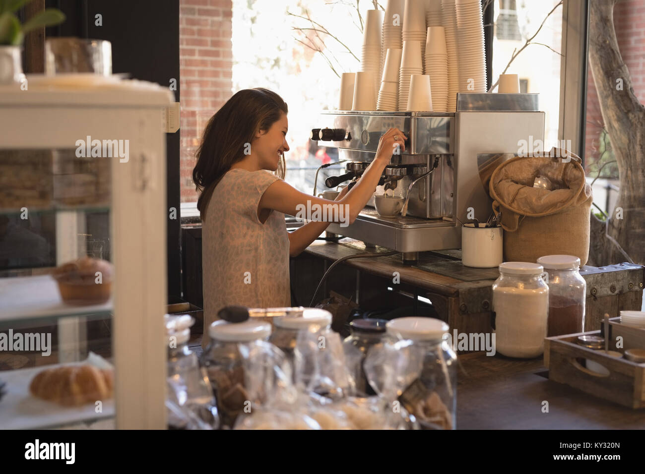 Smiling waitress making cup of coffee - Stock Image