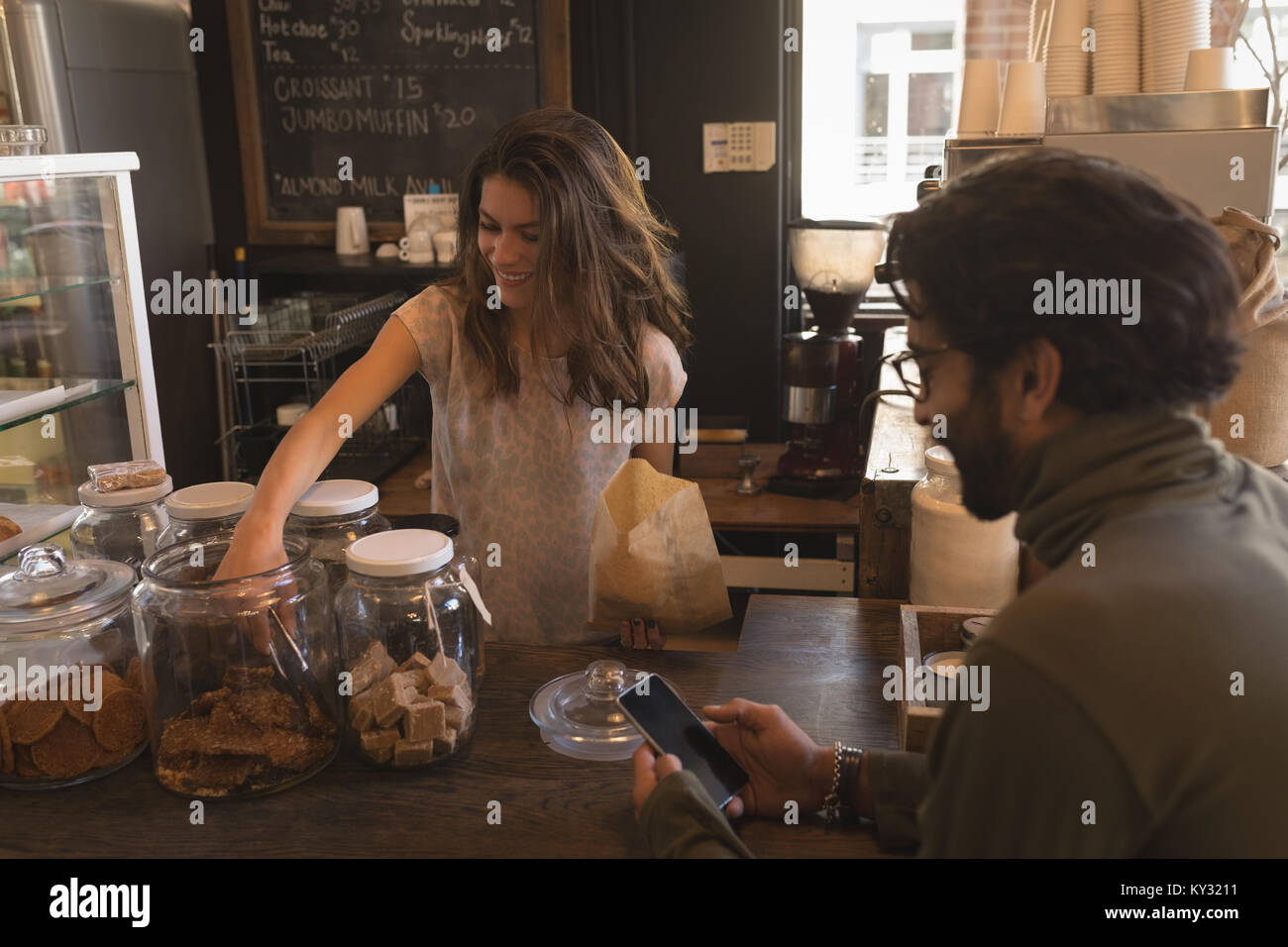 Waitress packing sweet food in paper bag - Stock Image