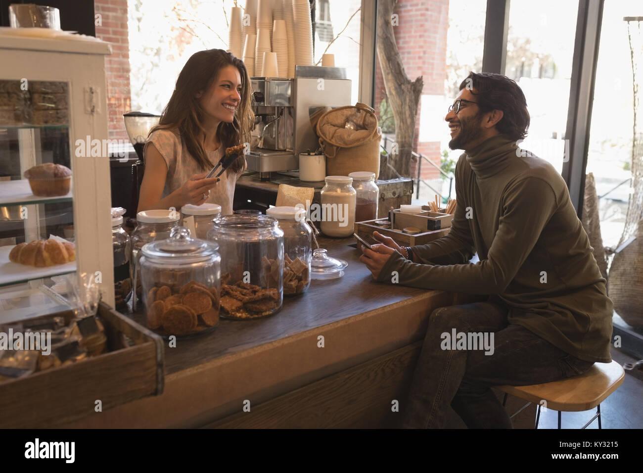 Smiling waitress talking to customer - Stock Image