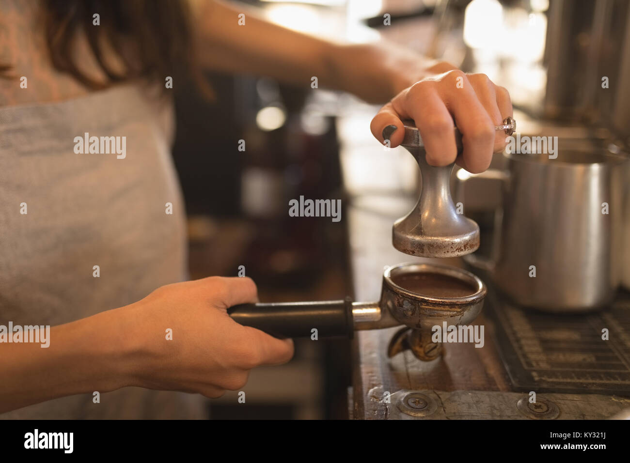 Barista using a tamper to press ground coffee into a portafilter - Stock Image