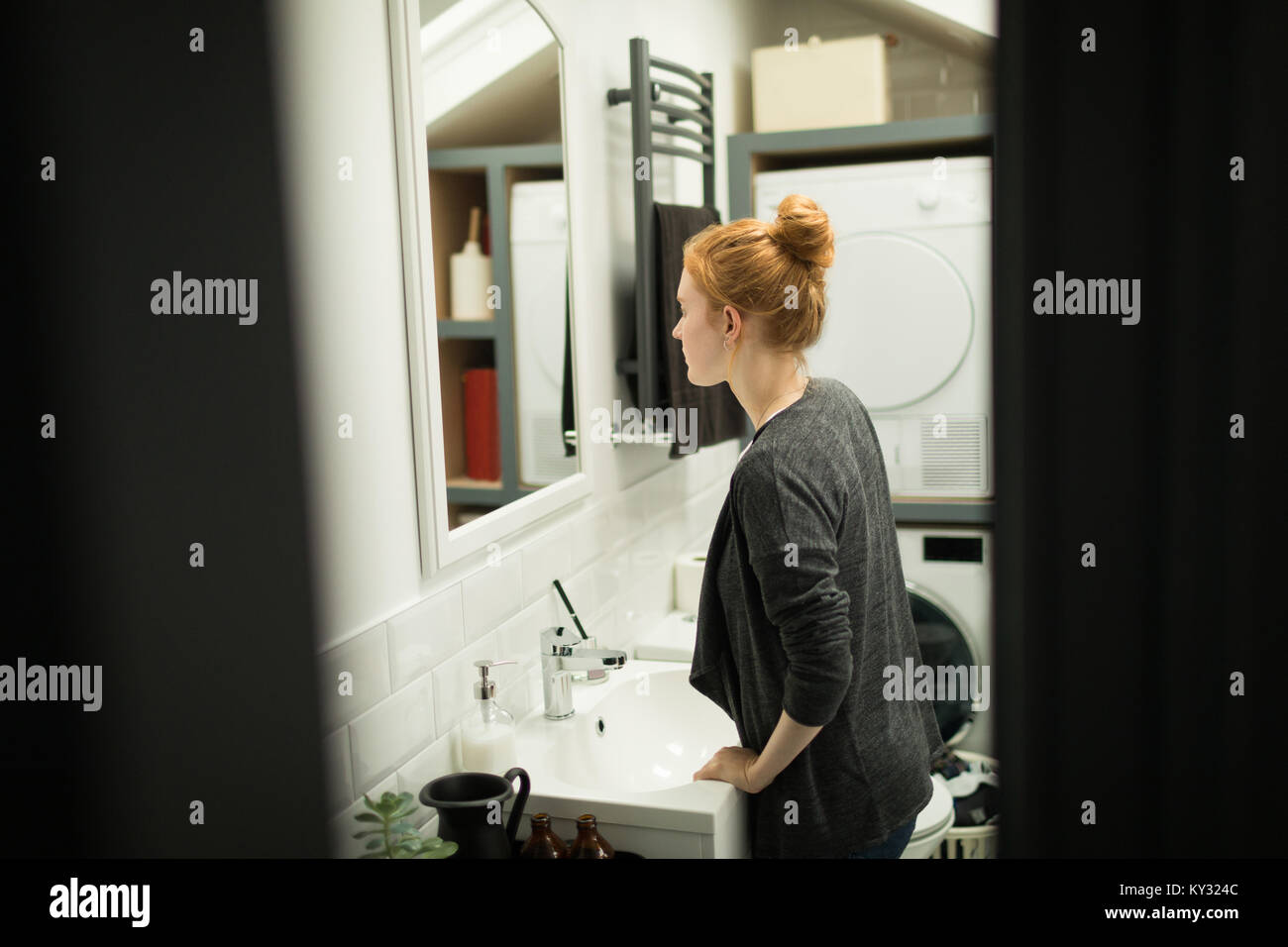 Young woman looking in bathroom mirror - Stock Image