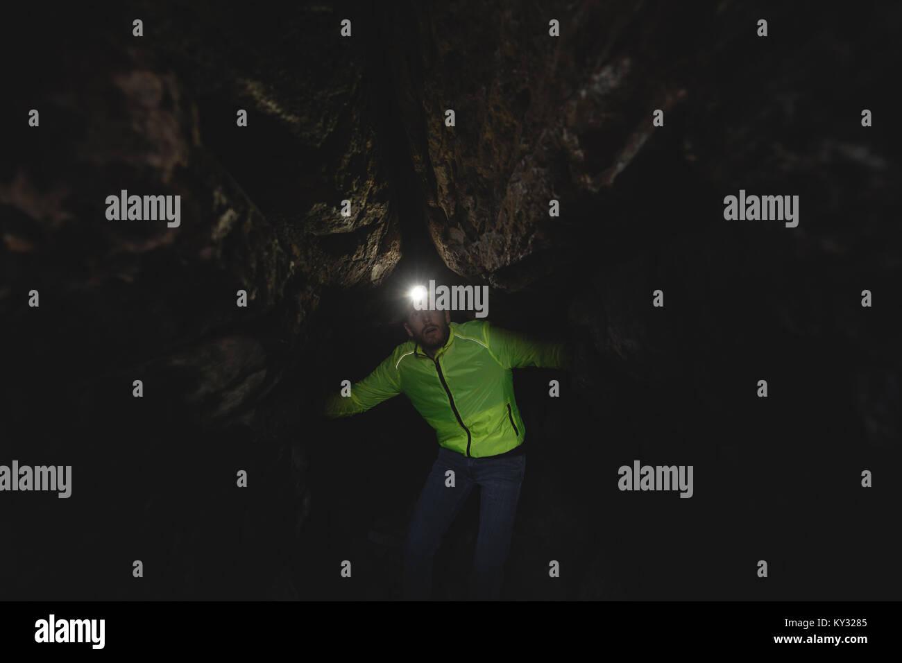 Hiker exploring cave - Stock Image