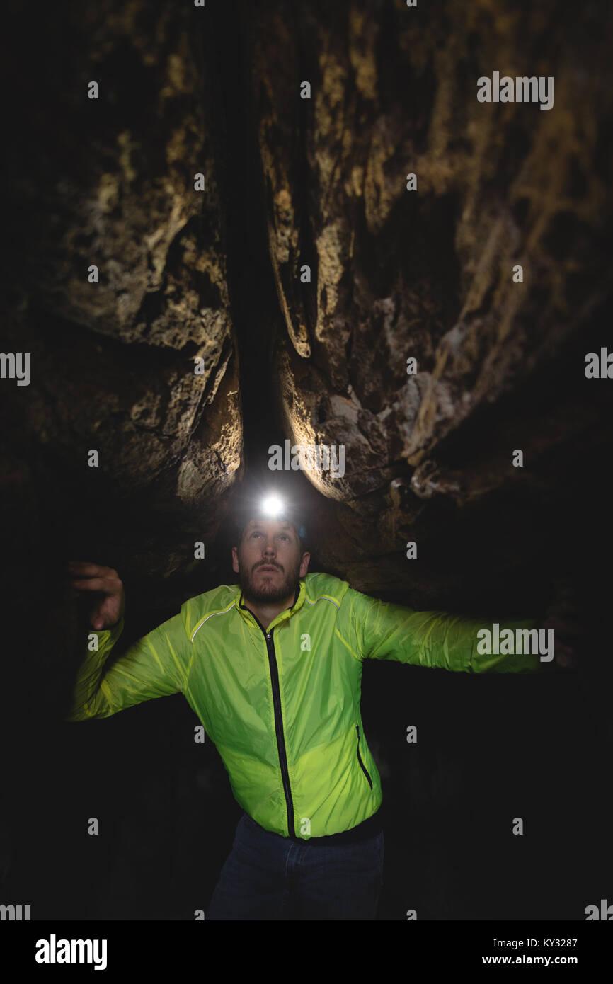 Hiker exploring the dark cave - Stock Image