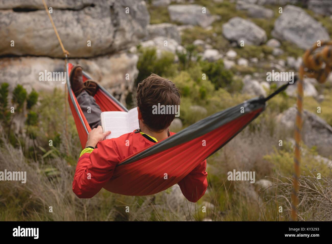 Hiker lying in hammock reading novel - Stock Image