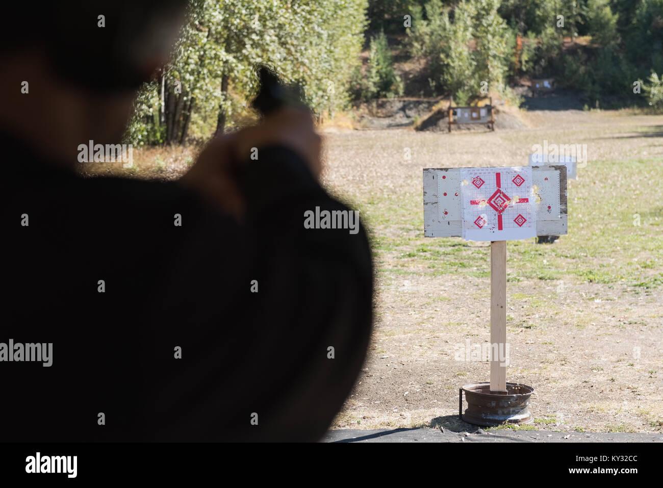Man aiming gun at target in shooting range - Stock Image