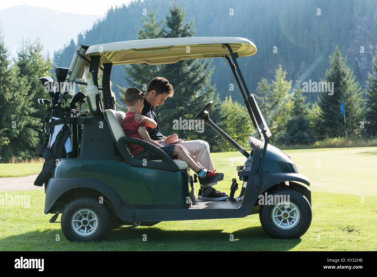 Father and son sitting in the golf cart - Stock Image