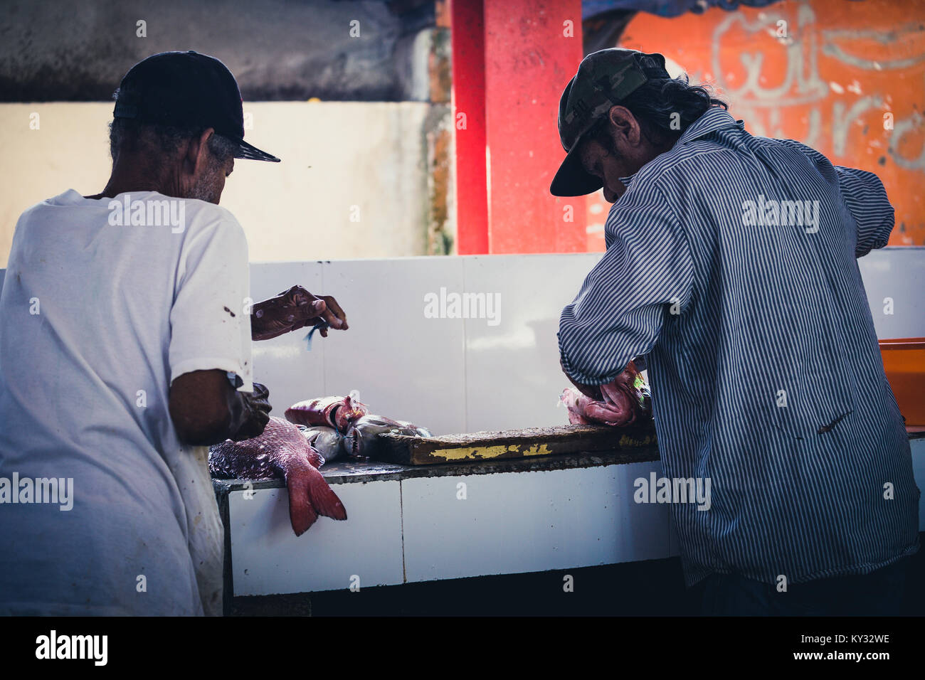 Two fishermen cleaning fish for sale on market, Victoria, Seychelles - Stock Image