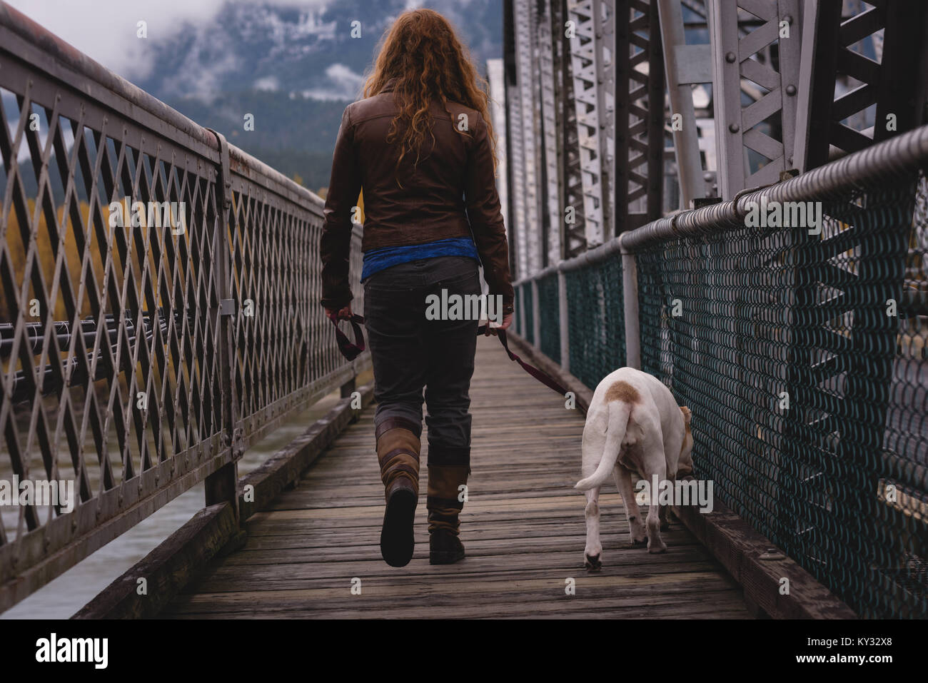 Woman walking on the bridge with her pet dog - Stock Image