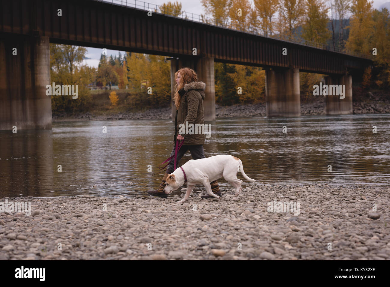 Woman with her pet dog walking by the river - Stock Image