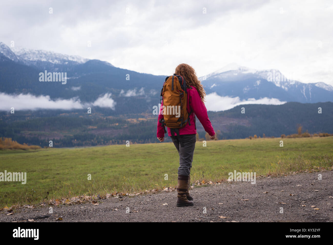 Woman walking on a dirt track against snow clad mountain and landscape - Stock Image