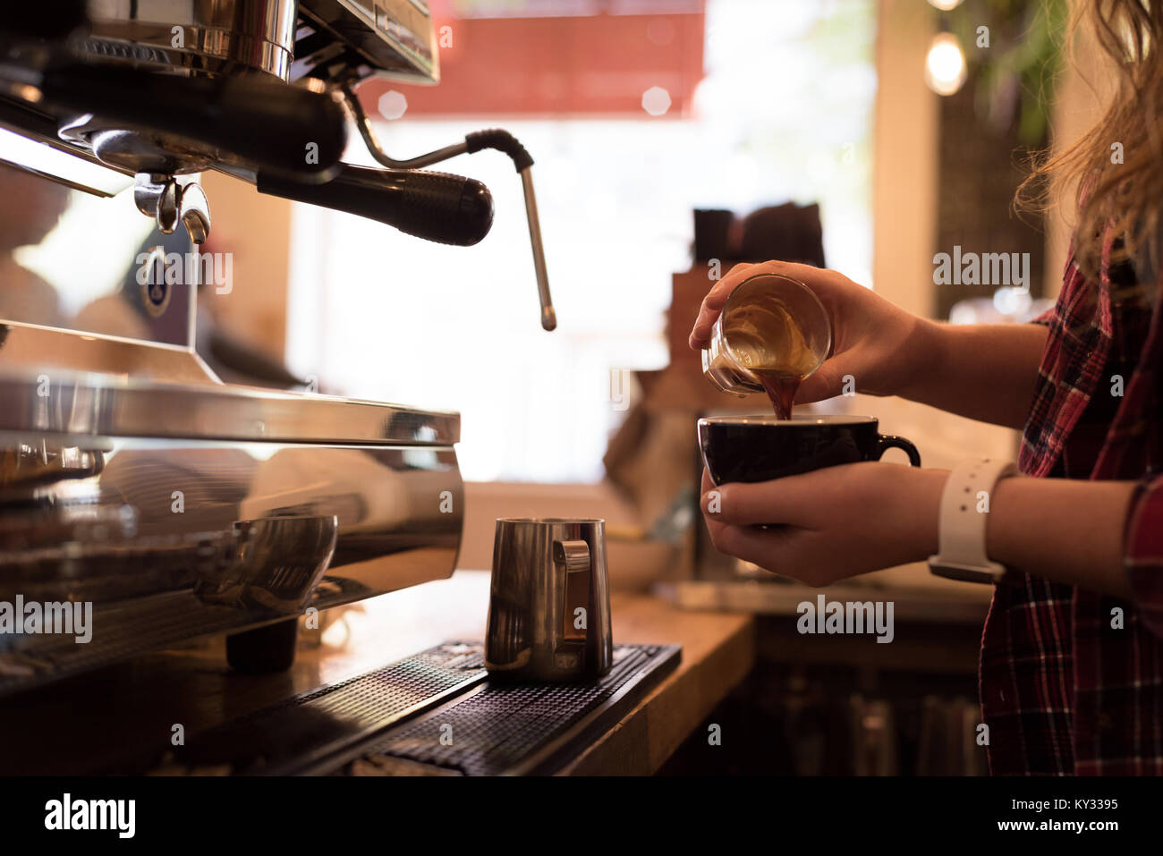 Mid section of barista pouring coffee in cup - Stock Image