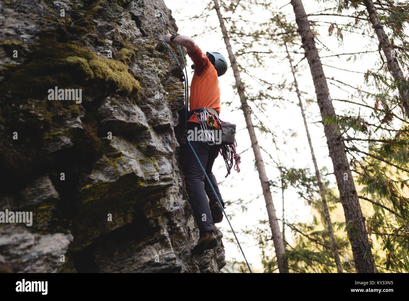 Rock climber climbing the rocky cliff - Stock Image