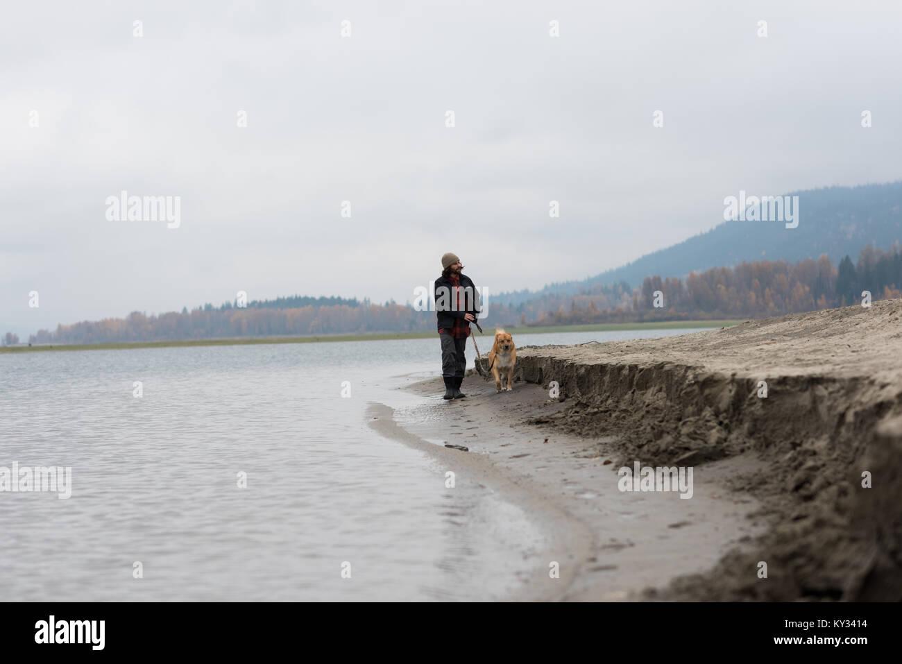 Man and his pet dog walking at river bank - Stock Image