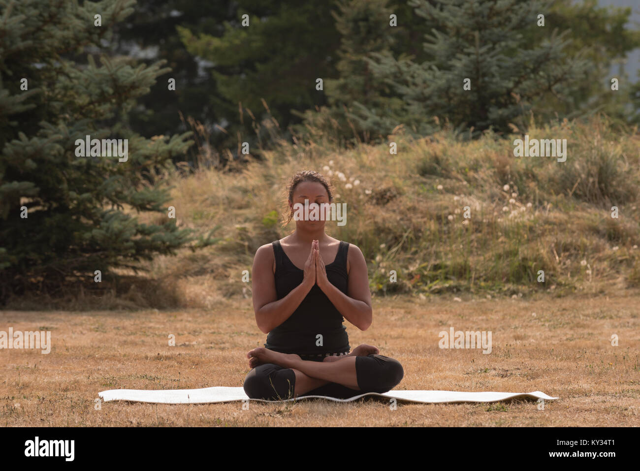 Fit woman sitting in meditating posture on an open ground - Stock Image