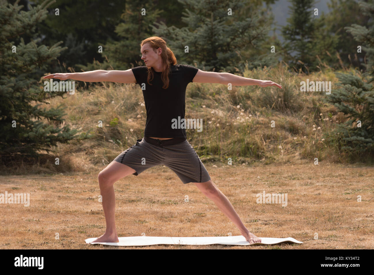 Fit man performing stretching exercise on an open ground - Stock Image