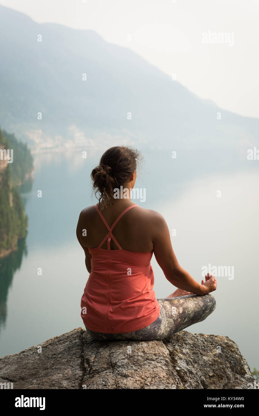Fit woman sitting in meditating posture on the edge of a rock Stock Photo