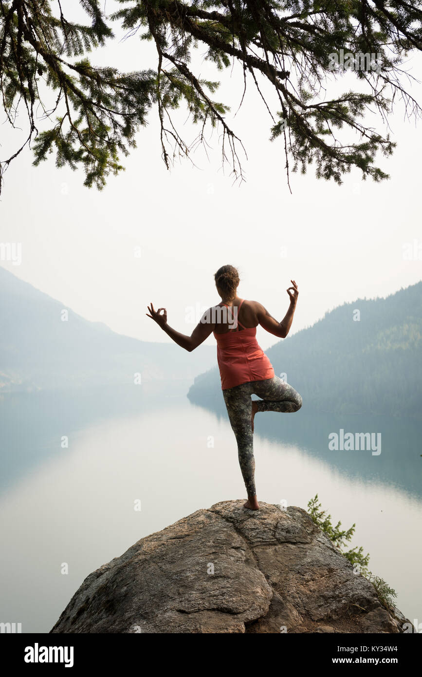 Fit woman balancing on one leg on the edge of a rock - Stock Image