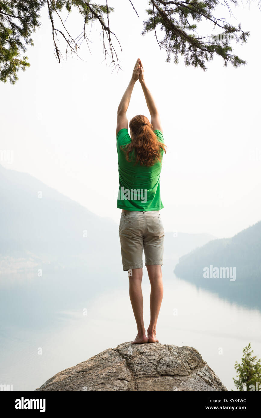 Fit man performing stretching exercise on the edge of a rock - Stock Image