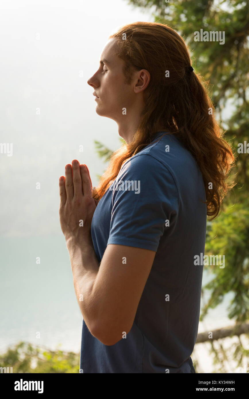 Fit man standing in meditating posture on the edge of a rock - Stock Image