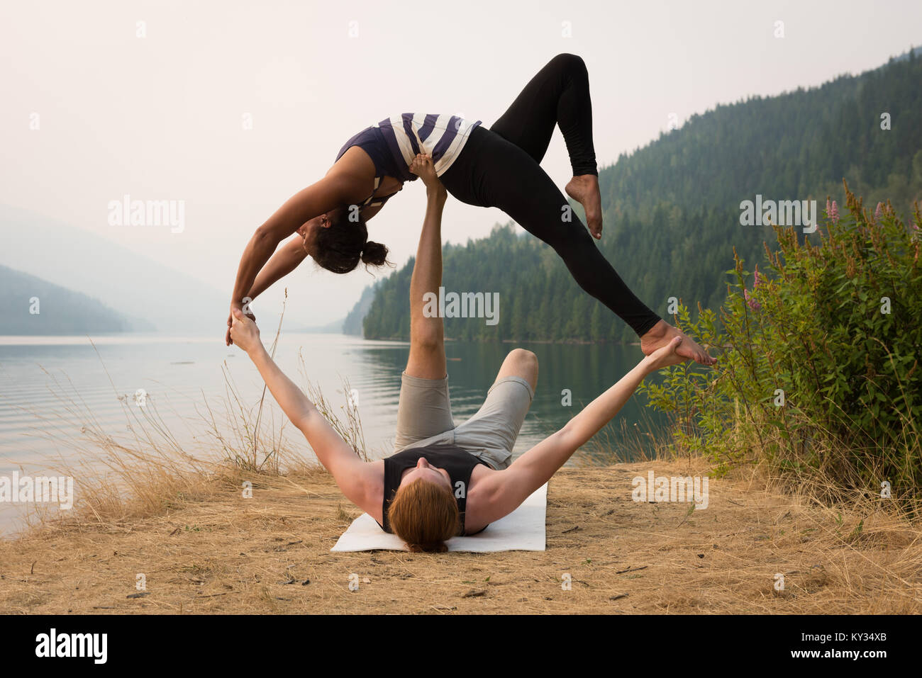 Fit couple practicing acro yoga in a lush green ground - Stock Image