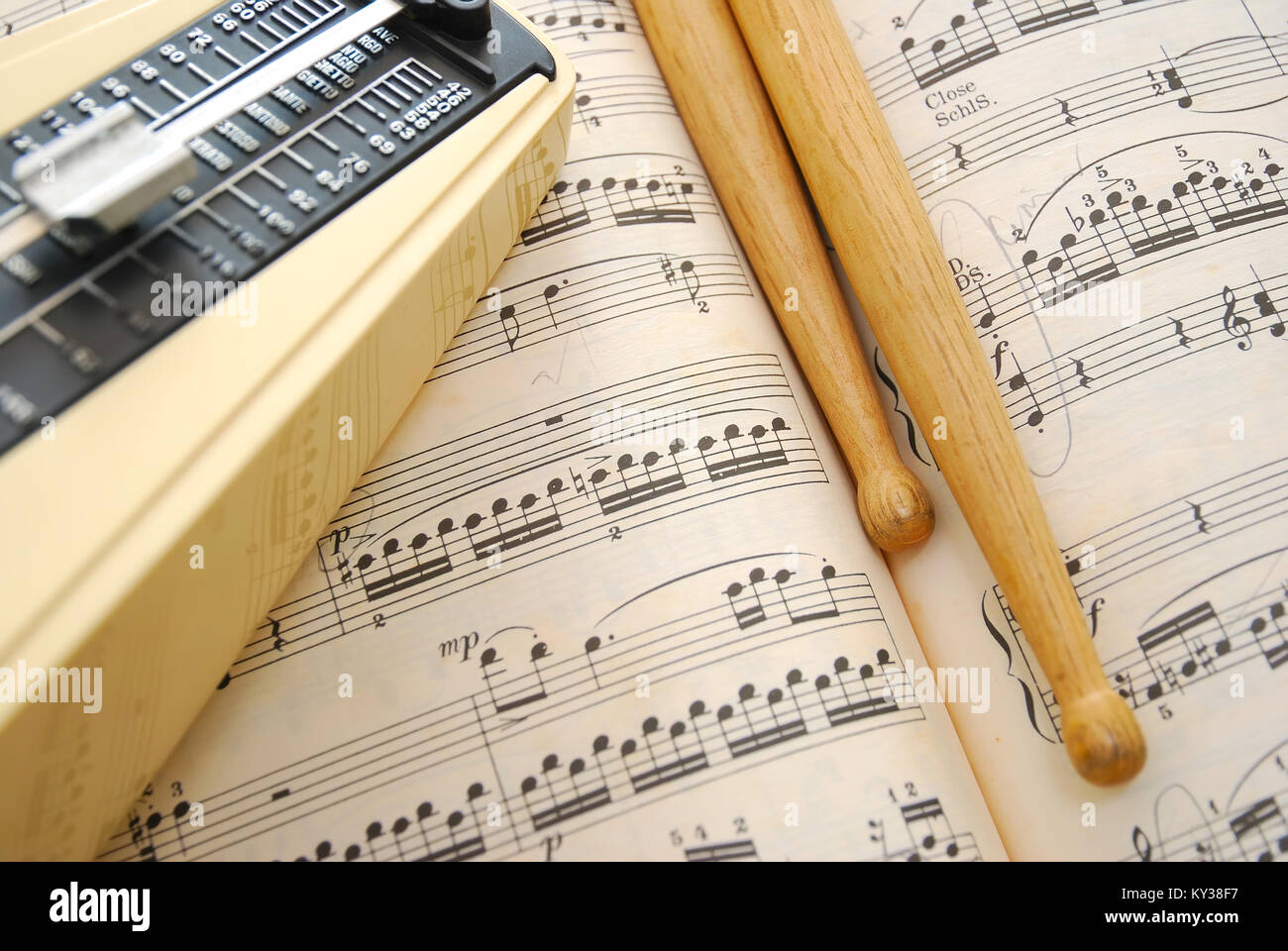 Music book, drum sticks and metronome. For concepts such as music and creativity. - Stock Image