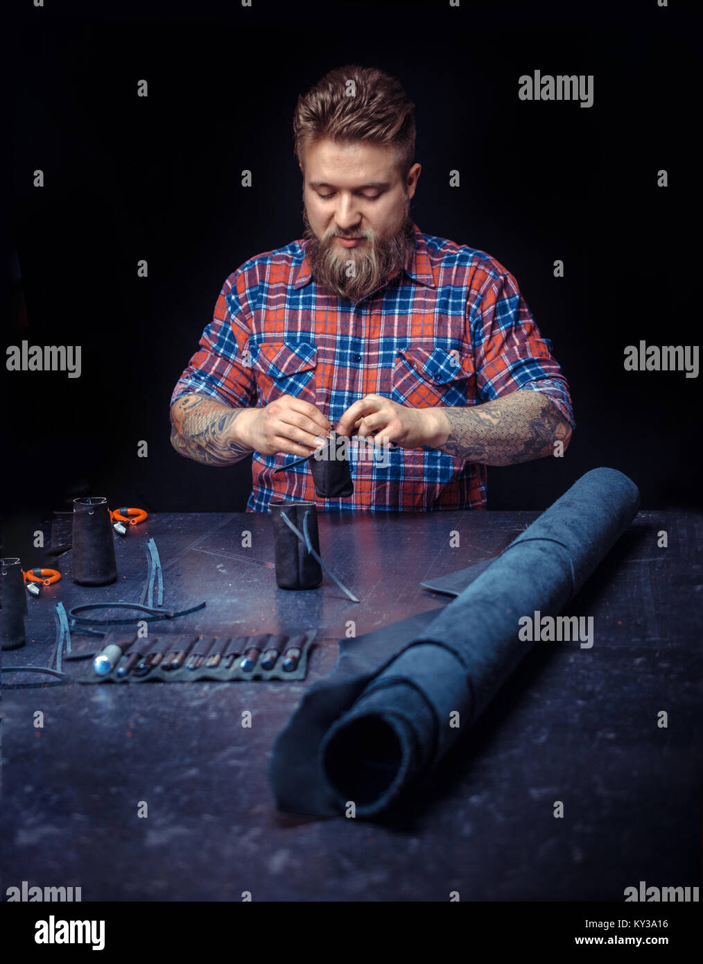 Leather cutter focusing on his work - Stock Image