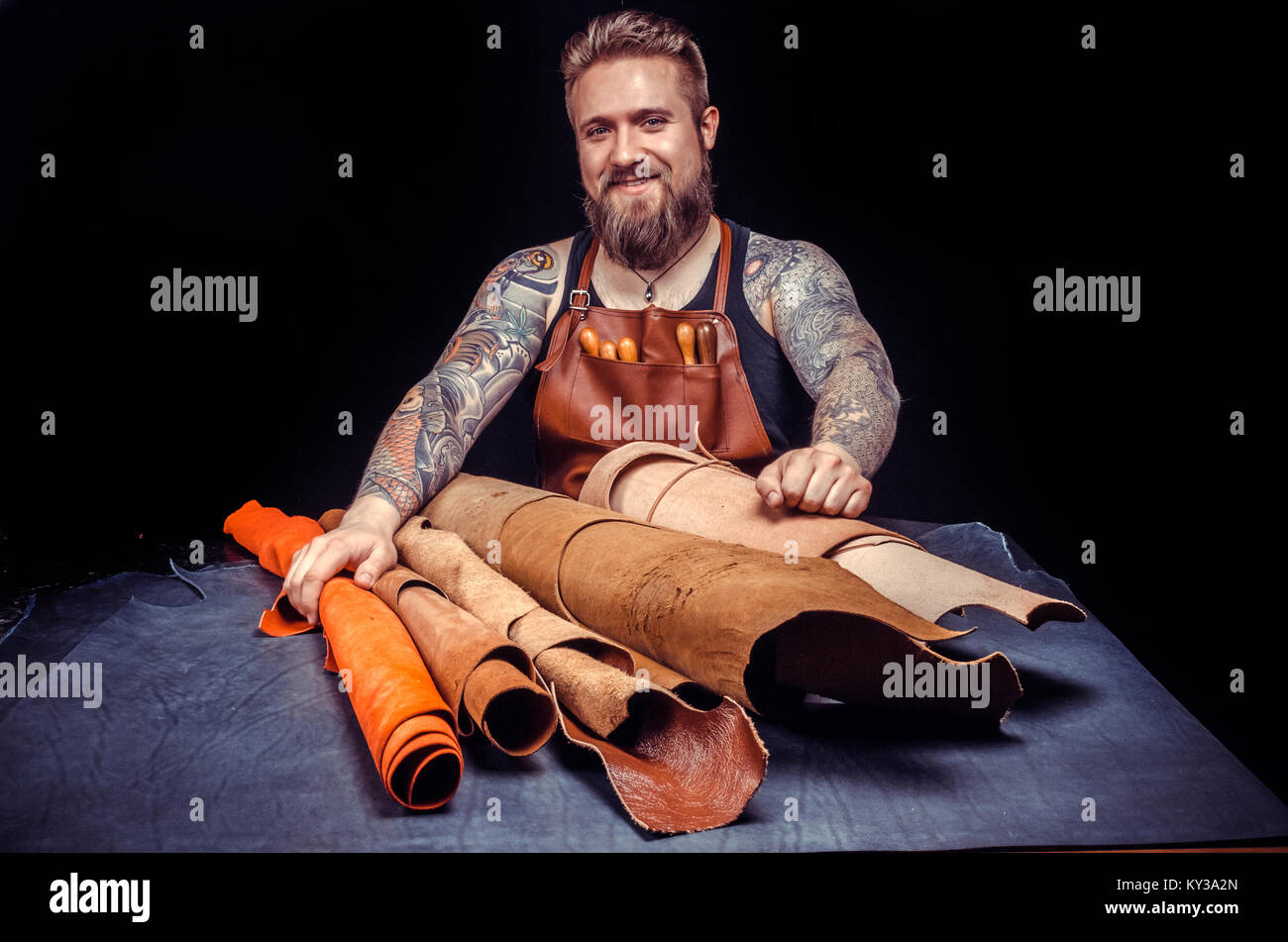 Man working with leather manufactures new product made of leather at his place of work - Stock Image
