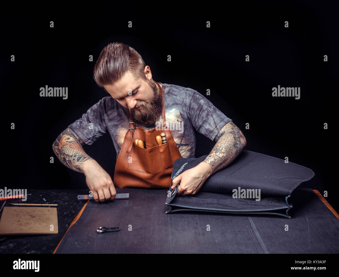 Leather Craftsman focusing on his work in his leather studio Stock Photo