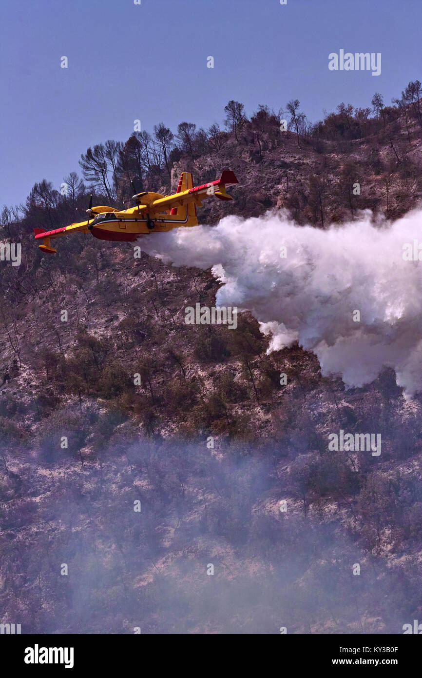 plane bombardier 415 discharge water on a fire - Stock Image