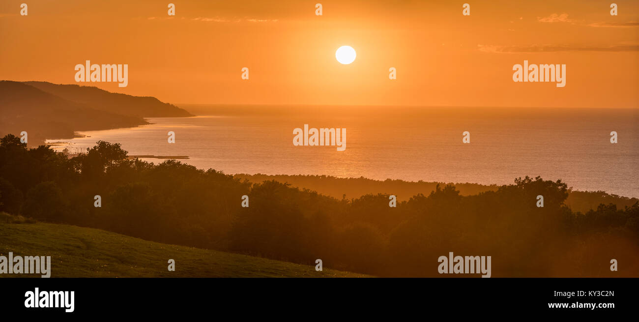 Sunset by the sea with the town of Bastad (Båstad) below. Panoramic view from the Hallandsas at the Bjare peninsula, Stock Photo