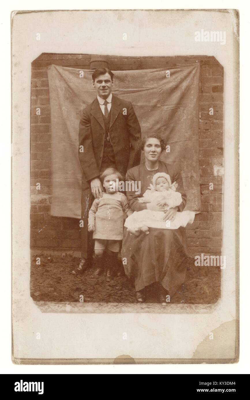 Early 1900s portrait photograph of family - possibly working class -  posing with a baby, outside in front of canvas, Stock Photo