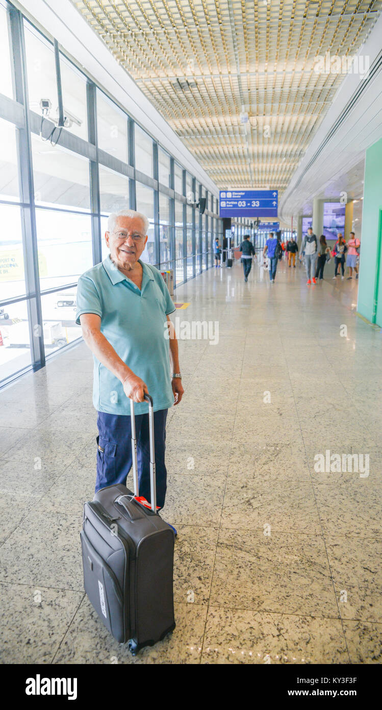 Model Released: Senior man (80-85) smiling while holding a hand luggage at a busy airport terminal - Concept: older - Stock Image