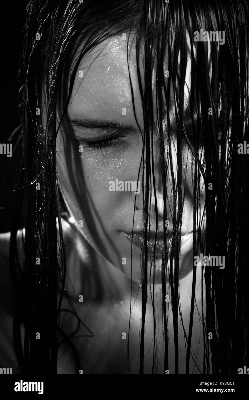 serious sad woman with wet black hair close her eyes in dark, monochrome - Stock Image