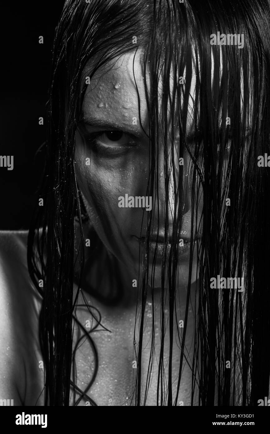 serious angry woman with wet black hair looking at camera, monochrome - Stock Image