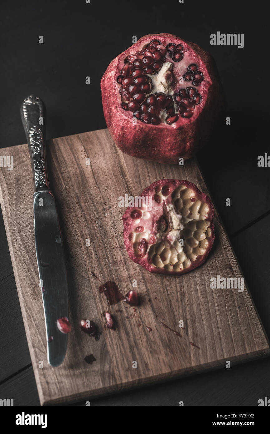 pomegranate and seeds freshly opened on wooden table - Stock Image