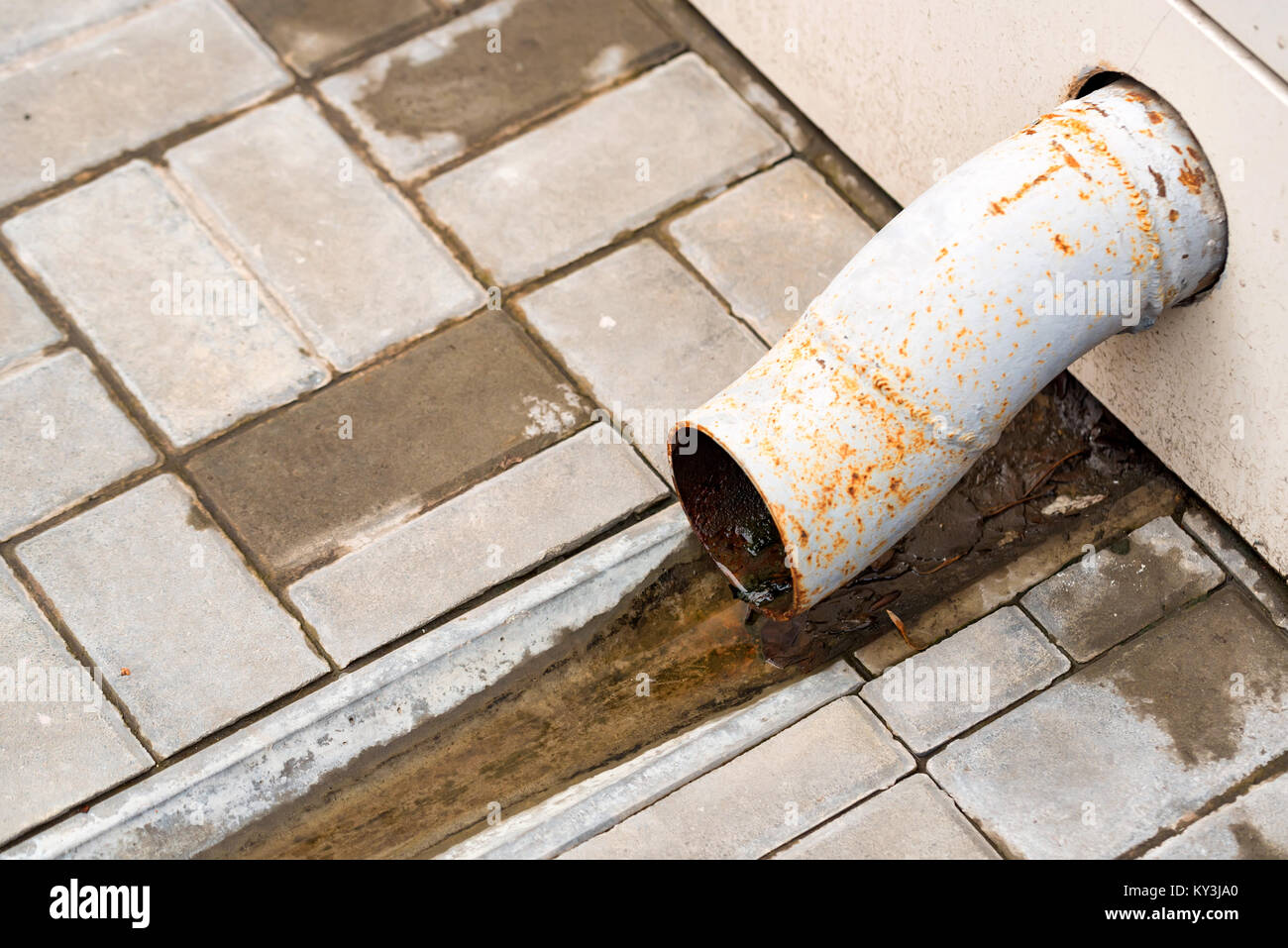 Small drain water pipe and pavement outdoors - Stock Image