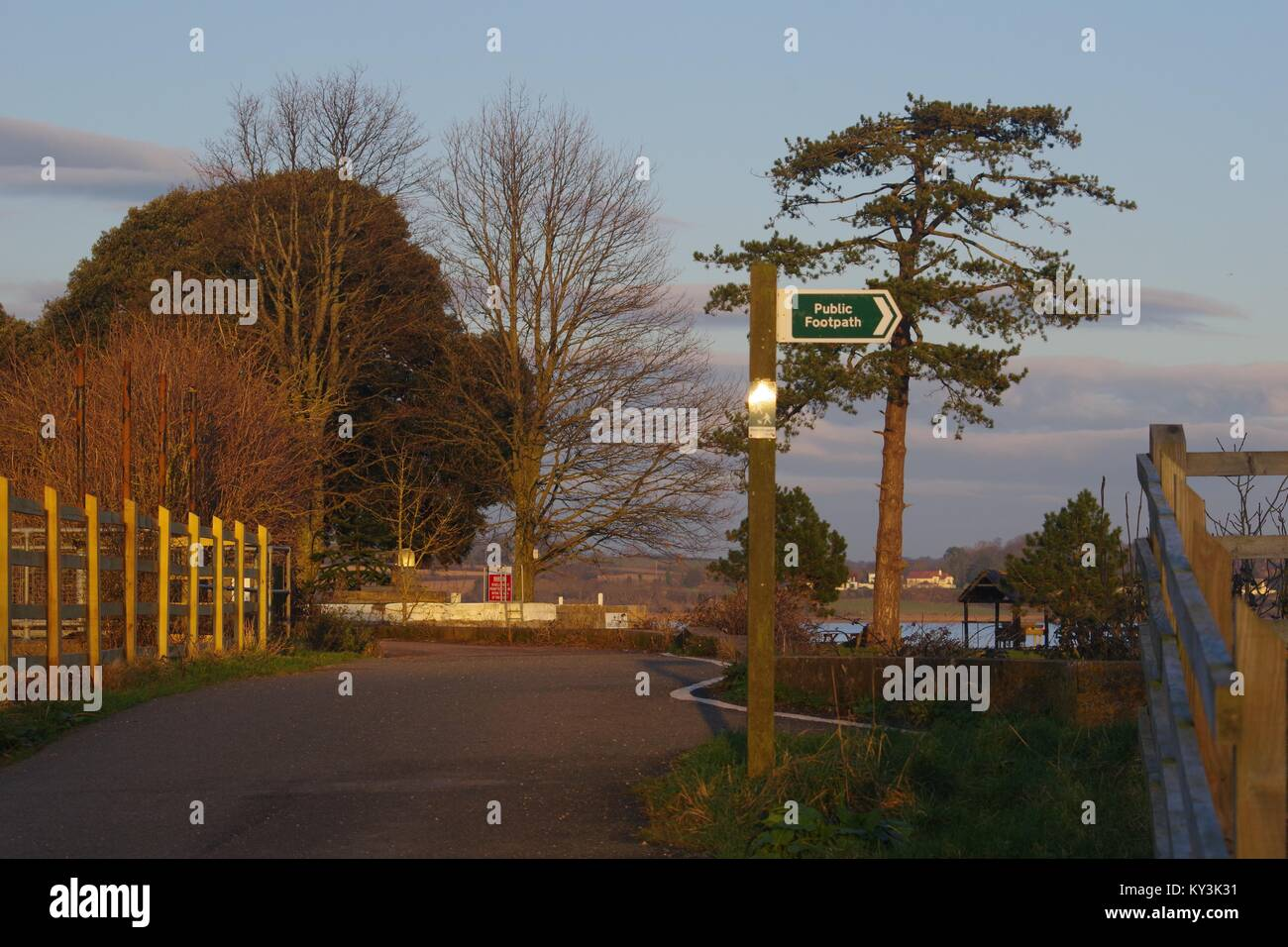 Public Footpath Signpost and the Exe Estuary Trail Cycle Path in the Golden Light of Sunset. Turf Lock Hotel, Exminster, - Stock Image