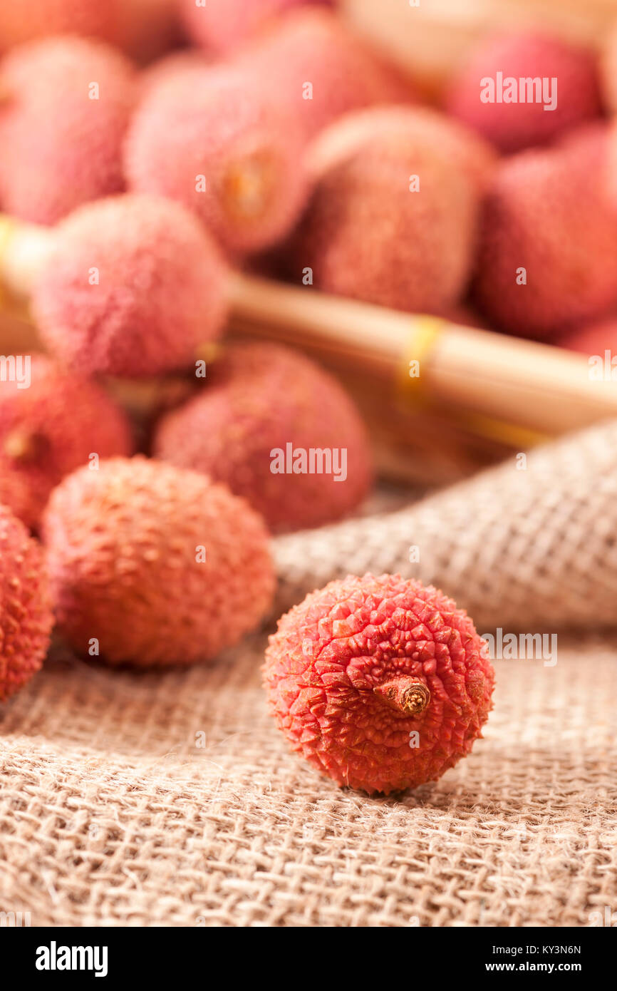 Studio shot with fruits (Lichi) of the lychee tree (Litchi chinensis) on coarse sackcloth fabric with a single sharply - Stock Image